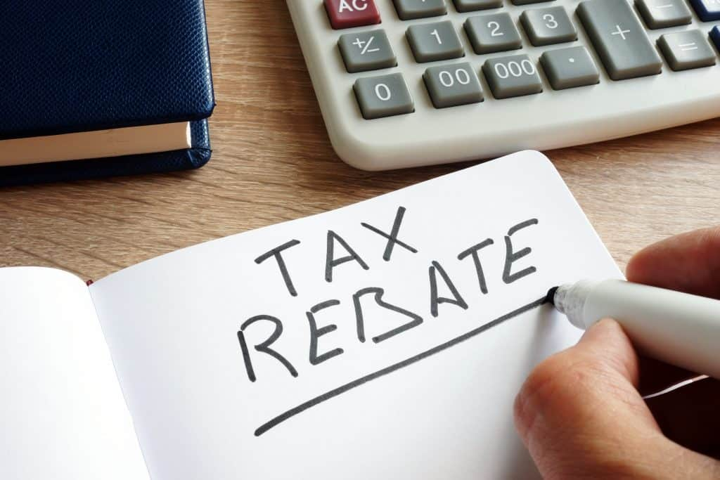 person with calculator writing tax rebate