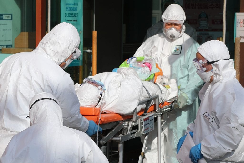 quarantine team wheeling a patient into the isolation ward