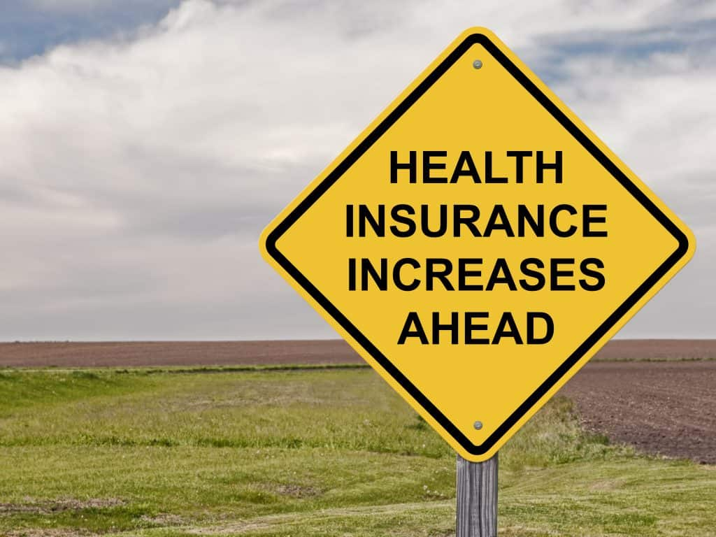yellow road sign showing health insurance increases ahead