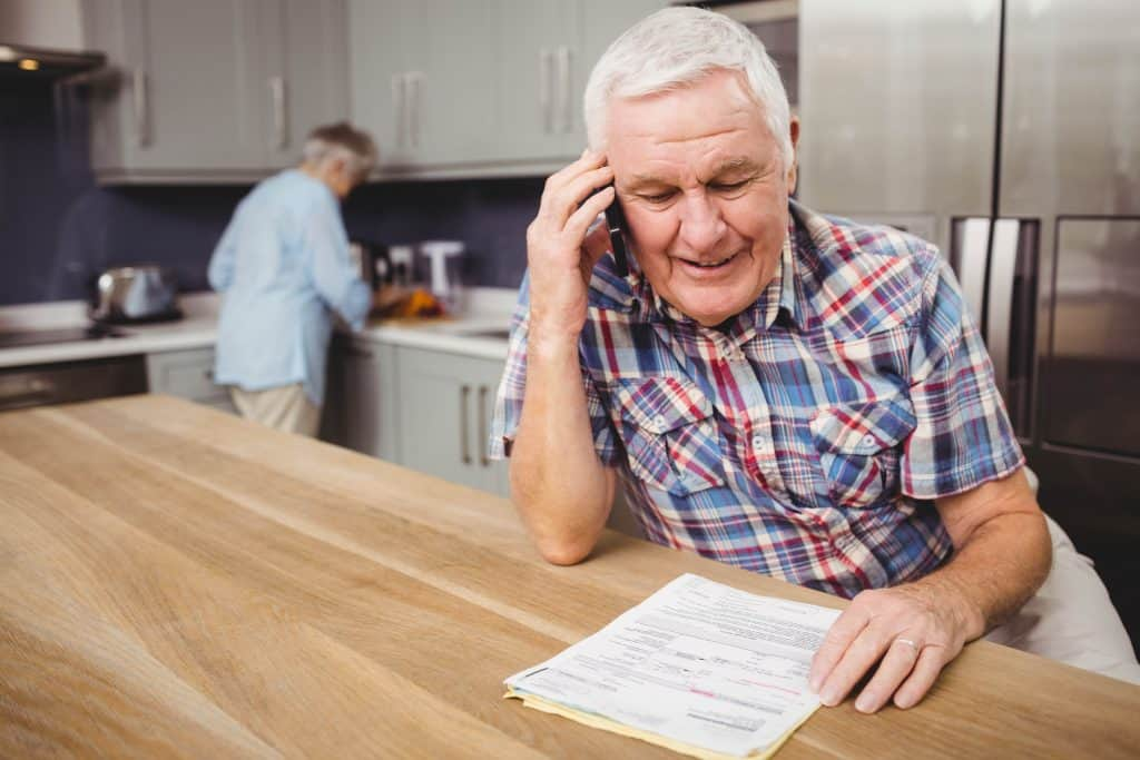 senior man holding bills on the phone and smiling