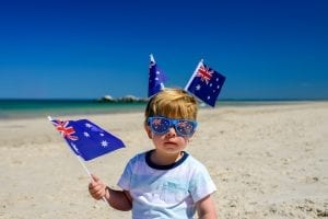 child on the beach waving wand wearing the Australian flag