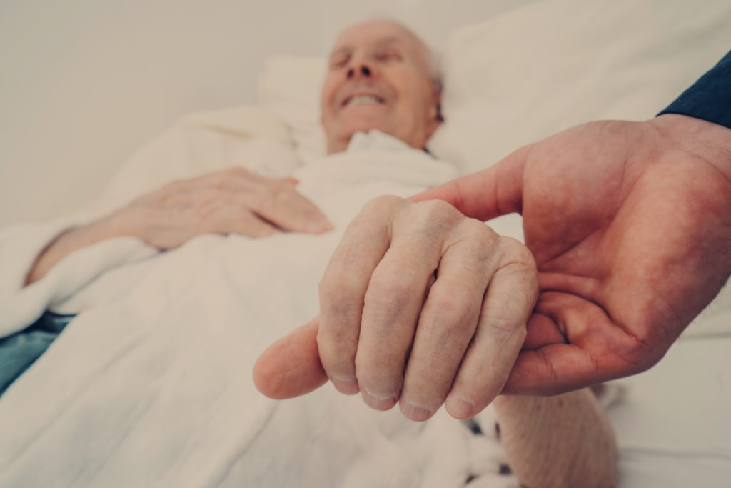 holding the hand of an elderly man in bed smiling
