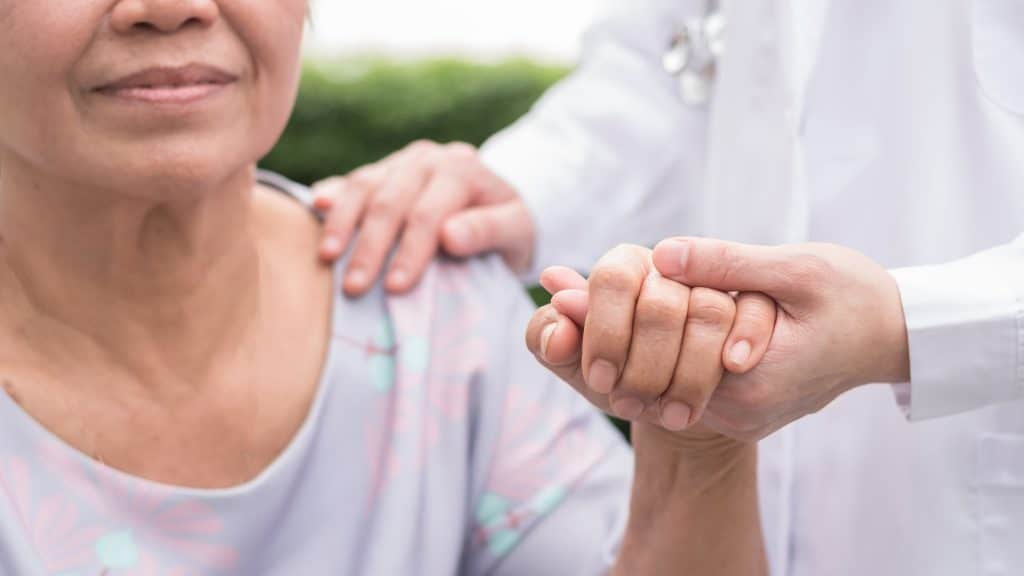 doctor holding hand of senior woman